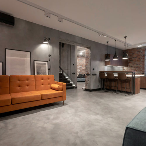 Modern spacious interior of studio flat including brown wooden kitchen with dinning furniture sets and soft orange couch with gray armchair against red brick and gray plastered walls in loft style